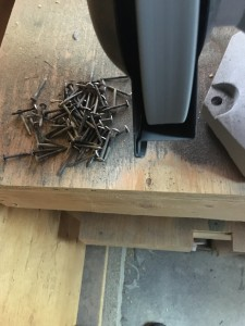A pile of rough arming nails next to the grinder